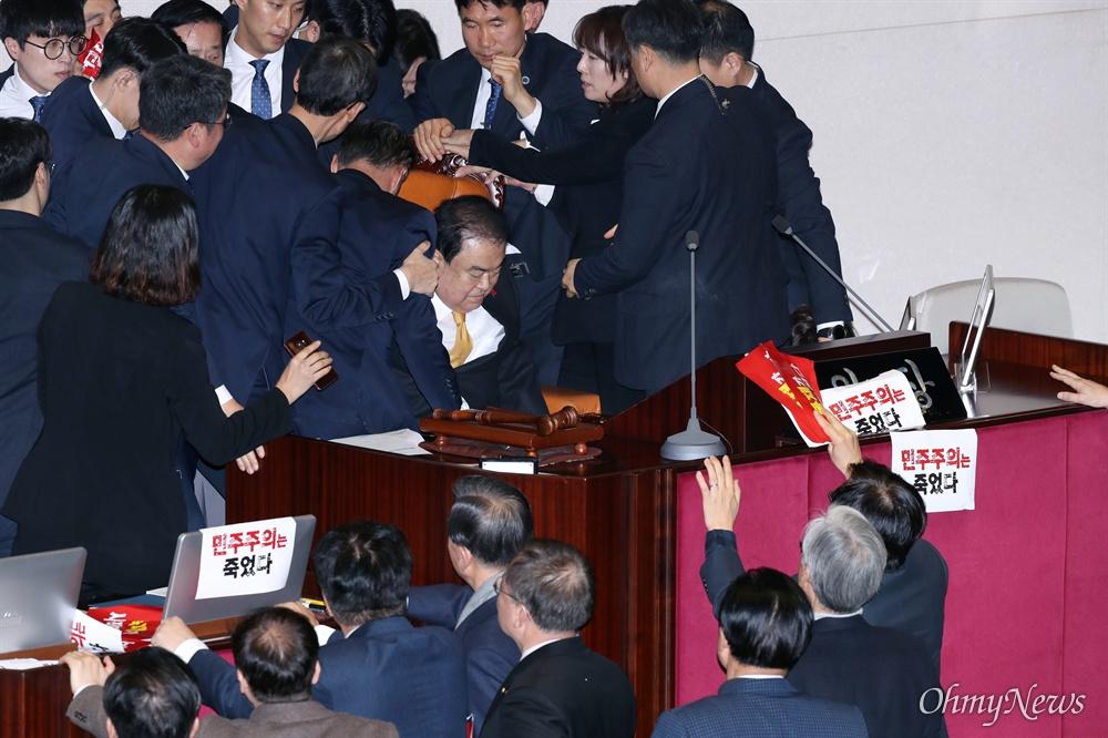 '휴~' 의장석에 겨우 앉은 문희상 의장 문희상 국회의장이 27일 오후 서울 여의도 국회 본회의장에서 자유한국당 의원들의 저지를 뚫고 의장석에 착석하고 있다.