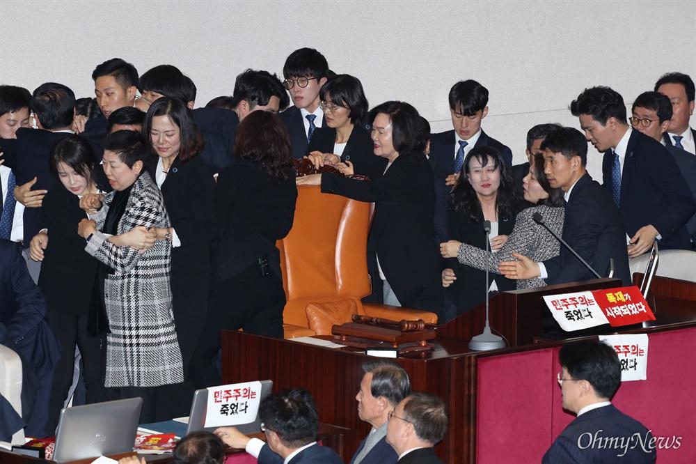 의장석 에워싼 한국당 의원들 자유한국당 전희경, 윤종필, 박인숙 의원 등이 27일 오후 서울 여의도 국회 본회의장에서 의장석을 에워싼 채 문희상 의장의 입장을 저지하고 있다. 질서유지권이 발동돼 국회 경위들이 자유한국당 의원들을 제지하고 있다.
