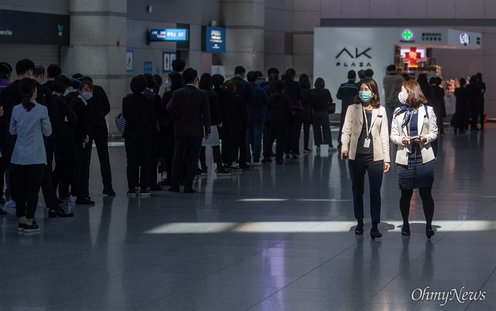 19일 오후 인천국제공항 제1터미널에서 상주 직원들이 마스크를 쓰고  마스크 구매 대기줄 옆을 지나고 있다.