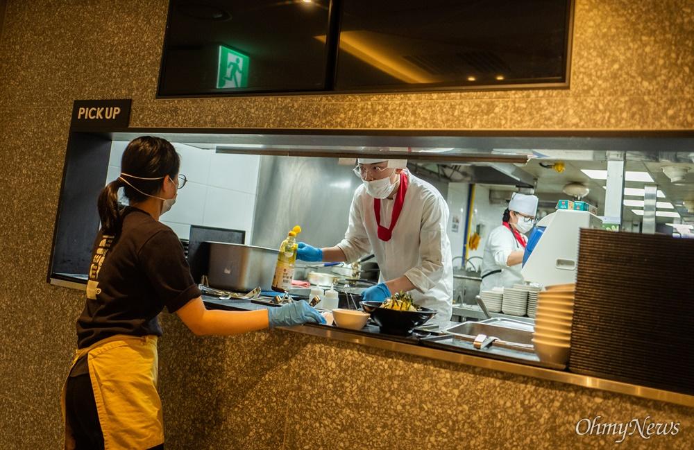 19일 오후 인천국제공항 제1터미널에서 근무하는 식당 직원들이 마스크를 쓰고 음식을 만들고 있다.