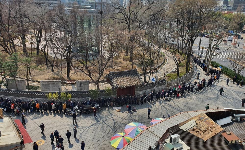 25일 서울 탑골공원 돌담길에는 많은 어르신들이 줄을 서서 무료급식을 기다리고 있다. 탑골공원은 2월 20일부터 문을 닫았다.