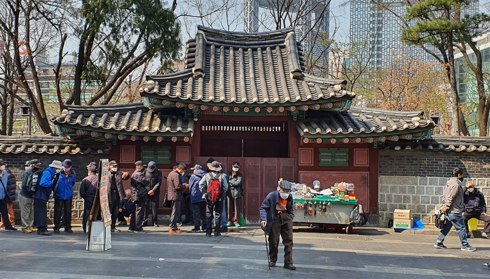 25일 서울 탑골공원 돌담길의 모습. 어르신들이 줄을 서서 무료급식을 기다리고 있다. 탑골공원은 2월 20일부터 문을 닫았다.
