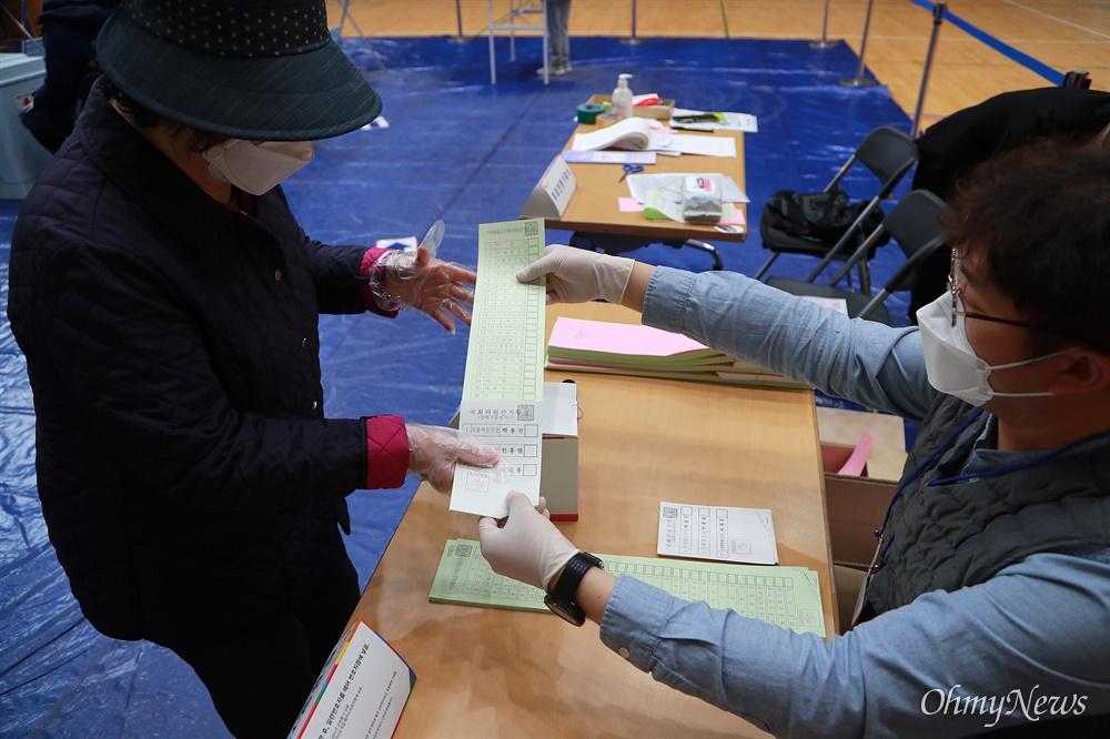 두 손으로 투표용지 전달