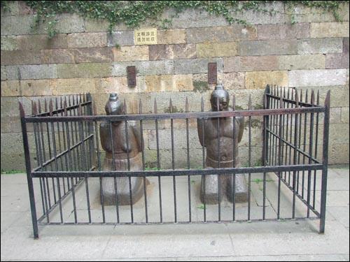 악비의 무덤 앞에 무릎꿇고 있는 진회와 그의 부인 왕씨.