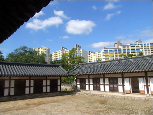 고택과 아파트  묵향 전시회가 열리는 은농재의 고택 뒤로 신축중인 포스코 아파트의 모습이 대조를 이루고 있다.