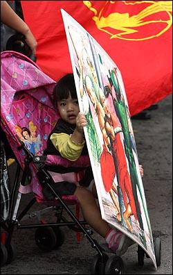 승려와 학생들의 평화시위를 유혈진압한 미얀마 군부를 규탄하는 집회가 27일 낮 서울 한남동 주한 미얀마 대사관 에서 버마민족민주동맹(NLD) 한국지부와 국내 인권단체 회원들이 참석한 가운데 열렸다. 엄마와 함께 나온 어린이가 군인들이 승려들을 탄압하는 그림을 들고 있다.