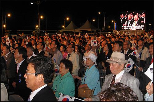 노 대통령의 귀환을 환영하기 위해 도라산 남북출입사무소 옆 광장에 모인 시민들이 일어나 태극기를 흔들며 '우리의 소원은 통일'을 부르고 있다.