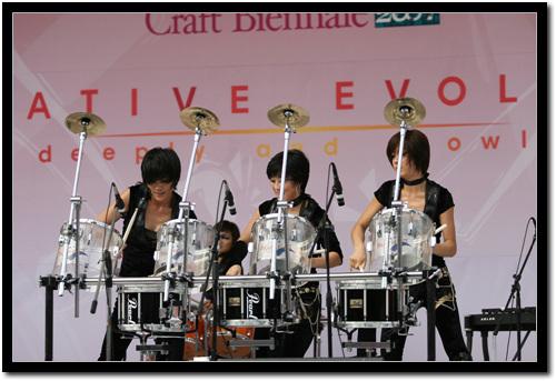3명이 드럼을 치는 모습  3명의 여성이 드럼 4개를 치고있는 모습