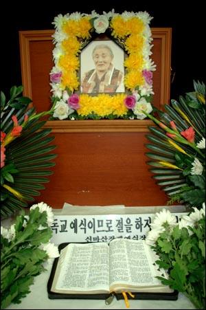 23일 밤 11시경 운명한 고 강도아 할머니의 영정 아래에 성경책과 국화꽃이 놓여 있다.