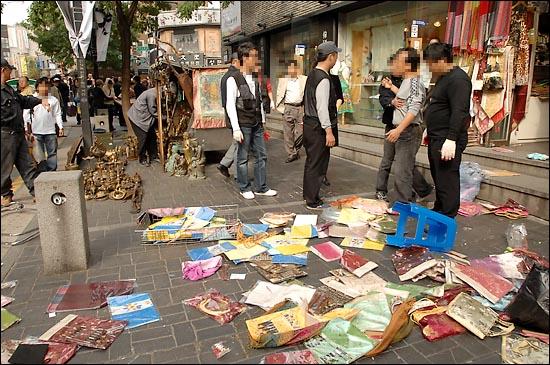물건을 '압류'당한 상인이 노점단속반에게 항의하고 있다.