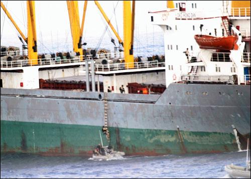 미 해군 구축함 제임스 E. 윌리엄스호의 승무원들이 30일 해적들을 제압하는 과정에서 다친 북한 선원들을 치료하기 위해 대홍단호에 오르고 있다.