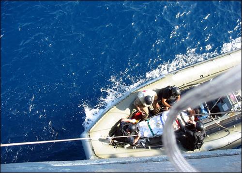 미 해군들이 제임스 E. 윌리염스호로 옮겨 치료를 한 북한 선원들을 대홍단호로 돌려보내고 있다.