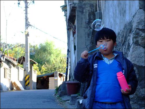 동네 한 편에서 한 꼬마가 비누방울 놀이를 하고 있었다.