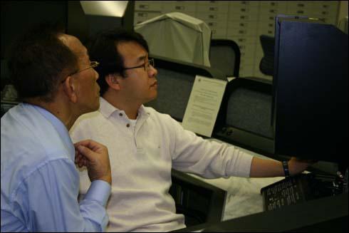 동포 유학생 권헌열(오른쪽)씨가 NARA 마이클로필름에서 한국관련 문서를 검색하자 그 곁에서 당시 시대상황을 설명해 주는 권중희 선생.