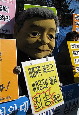 이건희 삼성그룹 회장의 탈을 쓴 기자회견 참가자가 '비정규직 짜르고, 비자금조성해서 죄송해요'라는 팻말을 들고 있다.