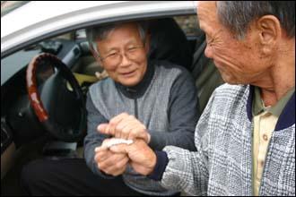 기노식씨(오른쪽)가 어머니의 친정 손자 고영준 선생에게 노잣돈을 전하고 있다.