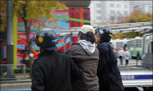 """""""빼빼로보다 중요한 그 무엇을 위하여""""  지난 11월 11일 <범국민행동의날> 집회에 참석했던 대학생이 전경들에게 연행되고 있다."""