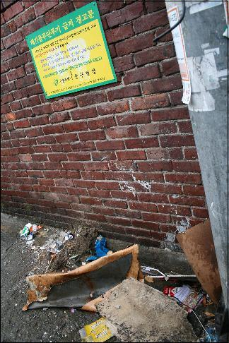 쓰레기 무단투기 금지 경고문 아래 쓰레기들은 어지럽게 널려있다.