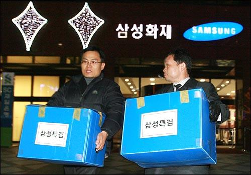 삼성특검 수사관들이 25일 저녁 서울 중구 삼성화재 본사에서 압수한 물품을 상자에 넣어 나오고 있다.
