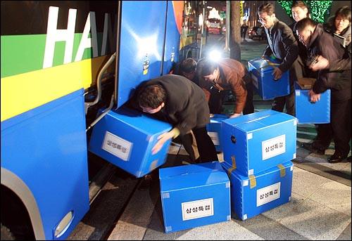 삼성특검 수사관들이 25일 저녁 서울 중구 삼성화재 본사에서 압수한 물품을 관광버스 화물칸에 차곡차곡 쌓고 있다.