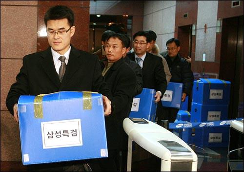 삼성특검 수사관들이 25일 저녁 서울 중구 삼성화재 본사에서 압수한 물품을 상자에 넣어 차량으로 옮기고 있다.