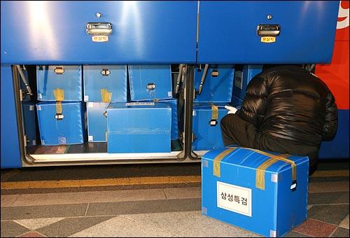 삼성특검 수사관이 25일 저녁 서울 중구 삼성화재 본사에서 압수한 물품을 관광버스 화물칸에 차곡차곡 쌓고 있다. 화물칸이 넘칠 정도로 상자가 많아서 일부는 승객용 의자에 실었다.