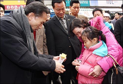 3일 오후 서울 관악구 봉천11동 원당시장을 방문한 이명박 당선인이 시장상인에게 산 떡을 한 어린이에게 나눠주고 있다.