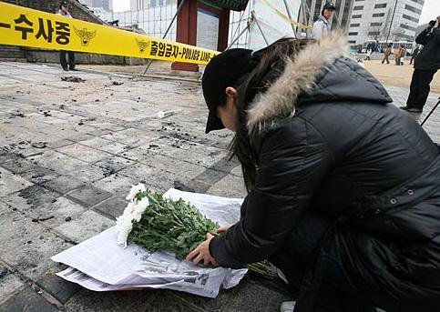 한 시민이 참담한 모습으로 변한 숭례문 앞에서 머리를 조아리고 있다.