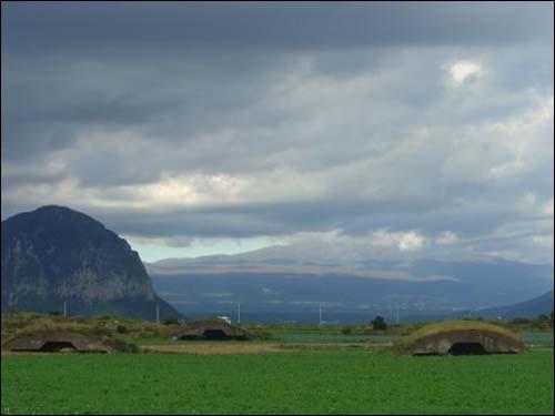 산방산.  산방산이 보이고 일제가 만든 비행장의 격납고가 보인다. 멀리 보이는 산이 한라산이다.