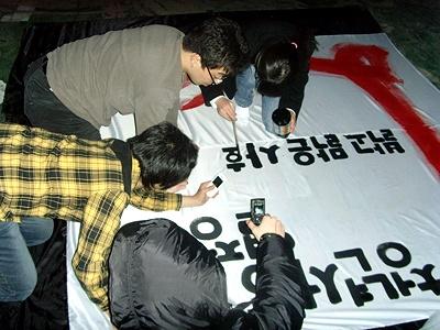 어두운 바깥에서 학생들이 깃발에 글씨를 쓰고 있다.