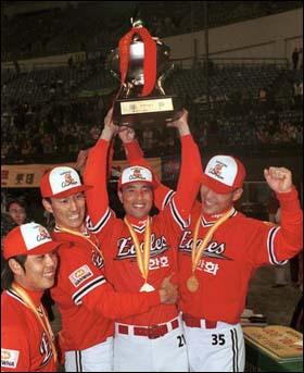 우승 1999년 우승. 주장인 강석천 선수(왼쪽에서 두 번째)가 송진우(가운데)와 함께 우승컵을 들어올리고 있다.