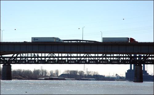 바지선은 없지만, 다리 위에는 대형 컨테이너 트럭이 오가고, 철교에도 화물을 실은 기차가 지나간다.
