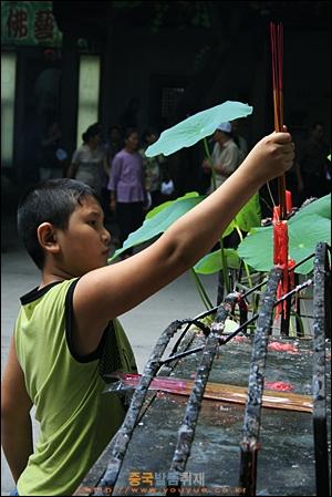 차오저우의 당나라 시대 사원 카이위엔쓰 천왕전 앞에서 향을 피우고 있는 아이