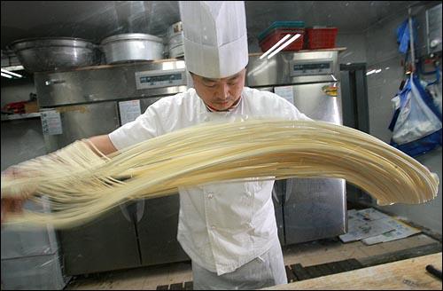 26일 낮 서울 마포구 한 중국요리집에서 주방장이 직접 손으로 면을 뽑고 있다.