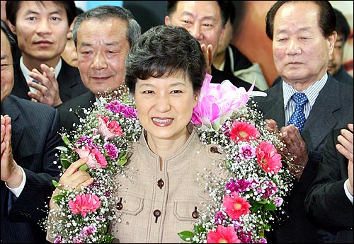 9일 한나라당 박근혜 전 대표가 당선이 확정되자 대구 달성군선거사무소에서 꽃다발과 함께 당원들의 축하를 받고 있다.
