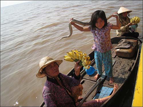 비단구렁이를 짊어지고 관광객들에게 바나나를 파는 아이와 할머니  수상촌이 관광지로 부각되면서 상당수 주민들은 관광객을 대상으로 행상을 하고 있다.