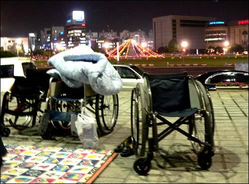 23일 밤 장애인들이 밤샘 노숙농성을 하고 있는 창원시청 현관 앞에 휠체어가 놓여 있으며, 그 앞에는 창원광장이 펼쳐져 있다.