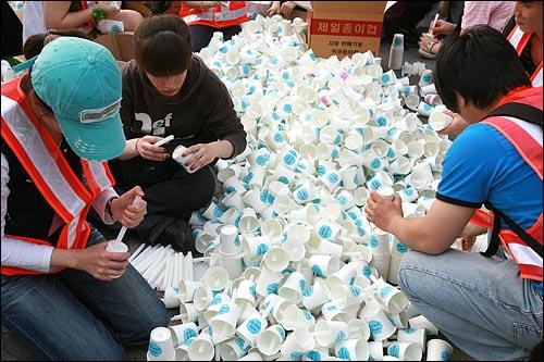 2일 저녁 서울 청계광장에서 미국산 쇠고기 전면 수입개방을 반대하는 촛불문화제가 열릴 예정인 가운데, 진행요원들이 시민들에게 나눠줄 초를 준비하고 있다.