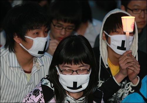 '이명박 탄핵을 위한 범국민운동본부' 주최로 6일 저녁 서울 여의도 공원 앞에서 열린 촛불문화제에서 학생들이 정부의 미국산 쇠고기 수입 정책 철회를 촉구하며 촛불을 들고 침묵시위를 하고 있다.