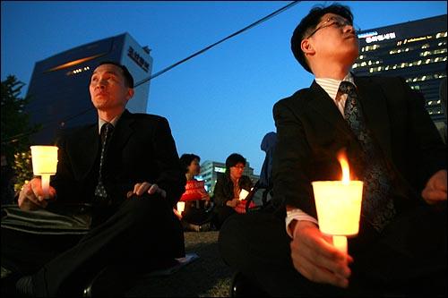 양복을 입은 직장인들이 6일 저녁 서울 청계광장에서 열리는 미국산 쇠고기 전면 개방을 반대하는 촛불문화제에 참여하고 있다.