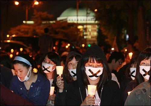 미국산 쇠고기 수입 전면 개방을 반대하는 학생과 시민들이 6일 저녁 서울 여의도 공원 앞에서 열린 촛불문화제에서 정부의 미국산 쇠고기 수입 정책 철회를 촉구하며 촛불을 들고 침묵시위를 하고 있다. 참가자 등뒤로 국회의사당이 보이고 있다.
