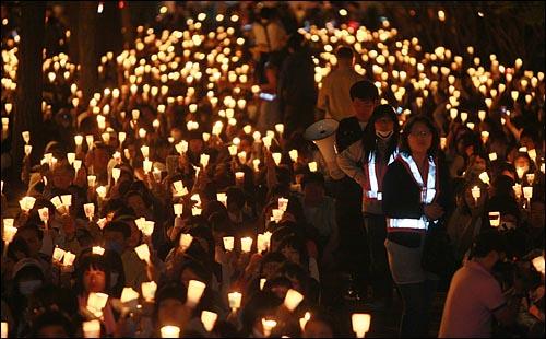 미국산 쇠고기 수입 전면 개방을 반대하는 학생과 시민들이 6일 저녁 서울 여의도 공원 앞에서 열린 촛불문화제에서 정부의 미국산 쇠고기 수입 정책 철회를 촉구하며 촛불을 들고 침묵시위를 하고 있다.