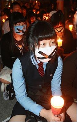 미국산 쇠고기 수입 전면 개방을 반대하는 학생들이 6일 저녁 서울 여의도 공원 앞에서 열린 촛불문화제에서 정부의 미국산 쇠고기 수입 정책 철회를 촉구하며 촛불을 들고 침묵시위를 하고 있다.