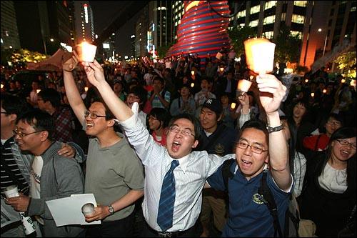 6일 저녁 서울 청계광장에서 열린 미국산 쇠고기 전면 개방 반대 촛불문화제에서 촛불을 든 시민들이 어깨동무를 한 채 흥겨운 노래를 부르고 있다.