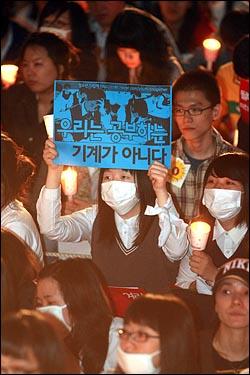 미국산 쇠고기 수입 전면 개방을 반대하는 촛불문화제가 열린 9일 저녁 서울 청계광장에서 한 여학생이 정부의 교육정책을 규탄하는 피켓을 들고 있다.