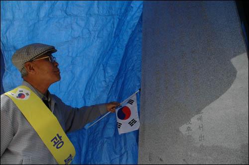 박성백 전 진주교대 교수가 위령비 옆면에 새겨진 탁경현의 약력을 읽어보고 있다.