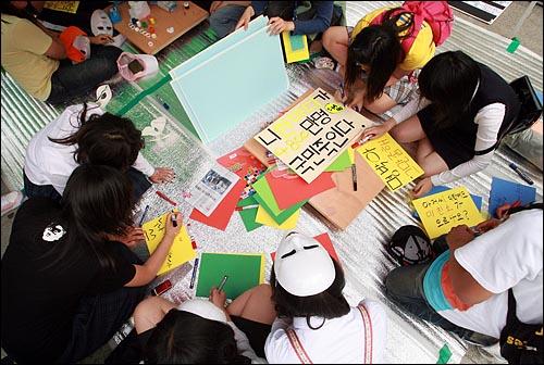 17일 오후 서울 덕수궁앞에서 열린 '미친소, 미친교육, 청소년이 바꾼다! 5.17 청소년 행동의날' 행사에 참석한 학생들이 색종이에 다양한 내용의 글을 직접 쓰고 있다.