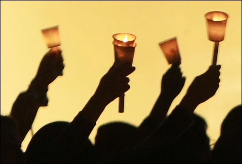 미국산 쇠고기 수입 전면 개방을 반대하는 학생과 시민들이 17일 저녁 서울 청계광장에서 열린 '5.17 미친소, 미친교육, 촛불문화제'에서 정부의 미국산 쇠고기 수입 정책 철회를 촉구하며 촛불을 들고 있다.