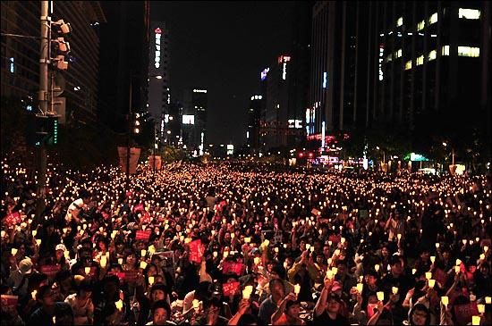 17일 저녁 서울 청계광장에서 열린 '5.17 미친소, 미친교육, 촛불문화제'에서 정부의 미국산 쇠고기 수입 정책 철회를 촉구하며 촛불을 들고 있다.