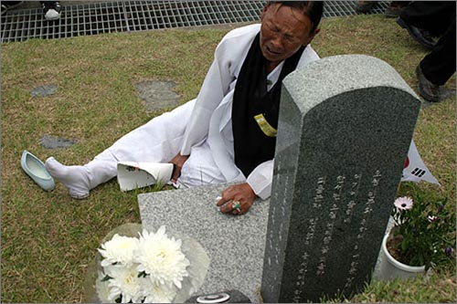 한 할머니가 고무신이 벗겨진 채 묘지앞에서 오열하고 있다.